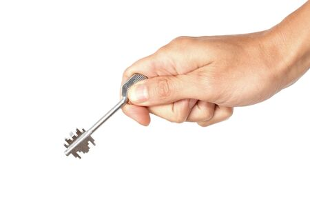 Metal key in the human hand, isolated on the white photo