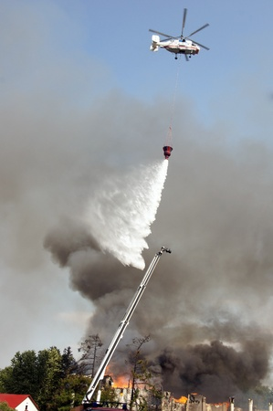 MOSCOW - AUGUST 30: Fire helicopters extinguish a fire in pavilion Veterinary fire at the All-Russia Exhibition Centre on AUGUST30, 2011 in Moscow