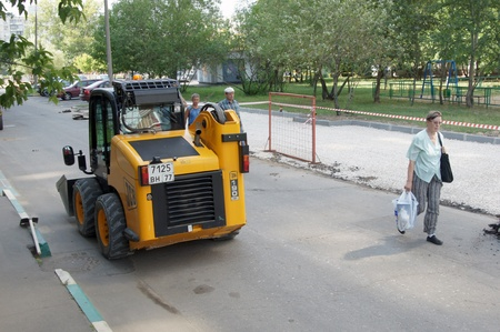 Workers repair road with minitractor use Stock Photo - 10484133