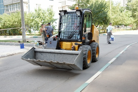 Workers repair road with minitractor use