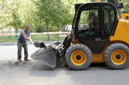 construction crew: Workers repair road with minitractor use