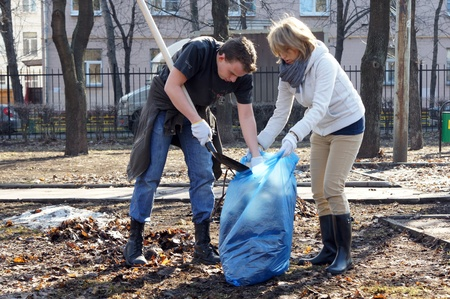 people clean fallen down leaves In park