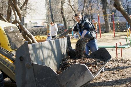 people clean fallen down leaves In park