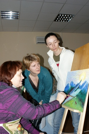 conducts: The teacher conducts lessons on painting with pensioners in the center of social service in Moscow