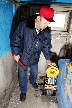 engine room: The mechanic makes planned repair of elevators in an apartment house Editorial