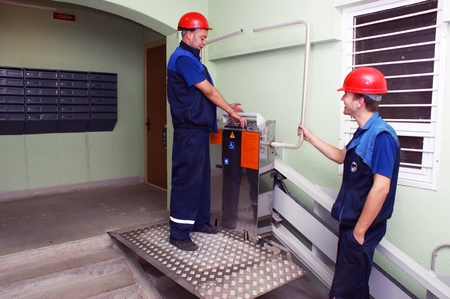 new age: Mechanics prepare for work the new lift for invalids in  apartment house Editorial