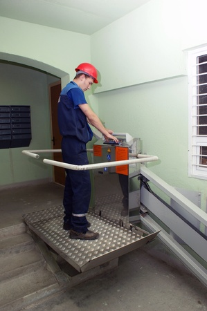 Mechanics prepare for work the new lift for invalids in  apartment house