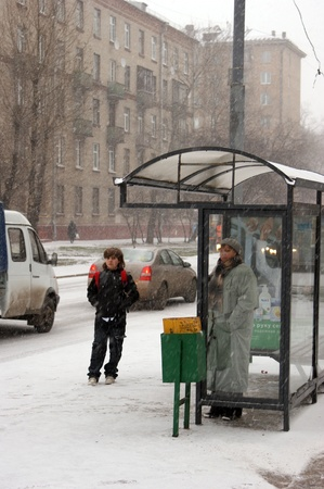 woman stop: People wait the bus at a snow covered stop Editorial