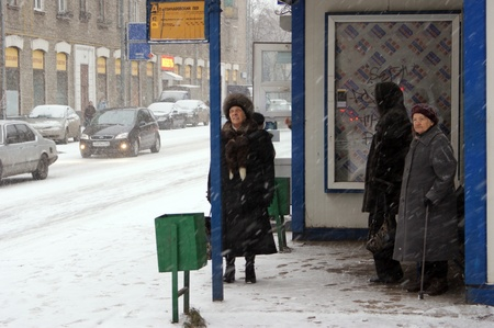 People wait the bus at a snow covered stop