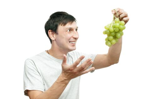 The young joyful man holds grapes in a hand Stock Photo - 10984352