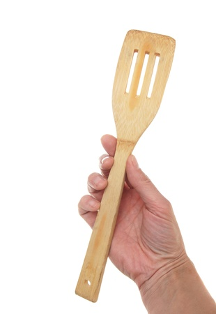 Wooden spoon in a hand, isolated on the white photo