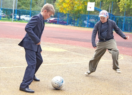 Two schoolboys play street football