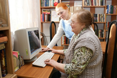 Two elderly women study the computer in the Center of social service in Moscow
