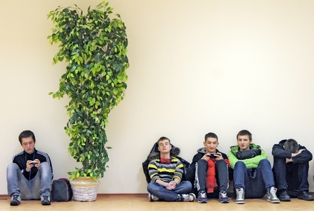 09 11 2011 Moscow  Young men sit on a floor at an empty wall indoors Stock Photo - 24217660
