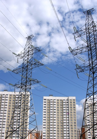Transmission line against the blue sky with clouds and modern apartment houses photo