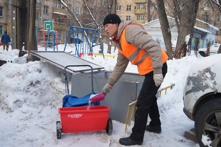 loads: 01 20 2012 Moscow. The worker of complex cleaning Loads a metering device against ice  reagent