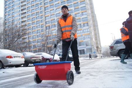 01 20 2012 Moscow. The worker of complex cleaning scatters against ice a reagent on road by means of a special metering device.