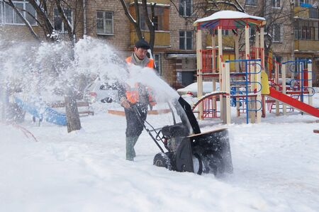 01 20 2012 Moscow. The worker of complex cleaning cleans snow from a path by means of the motor block. Stock Photo - 12159958