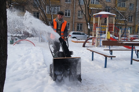 01 20 2012 Moscow. The worker of complex cleaning cleans snow from a path by means of the motor block.