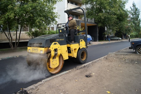 Packing of a new asphalt covering on road before an apartment house within the limits of the city program of an accomplishment of domestic territories, on september 30, 2011, in Moscow. Stock Photo - 12201090