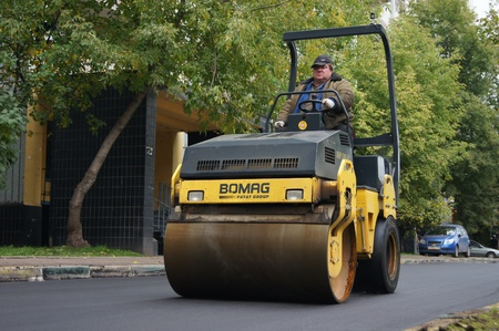 Packing of a new asphalt covering on road before an apartment house within the limits of the city program of an accomplishment of domestic territories, on september 30, 2011, in Moscow.