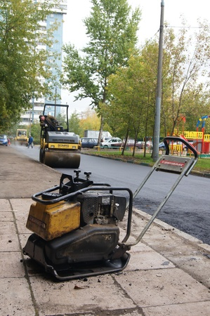 Packing of a new asphalt covering on road before an apartment house within the limits of the city program of an accomplishment of domestic territories, on september 30, 2011, in Moscow. Stock Photo - 12201101