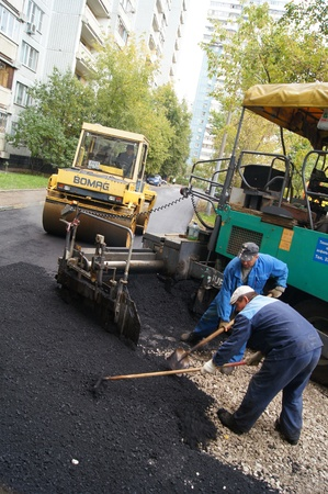 Packing of a new asphalt covering on road before an apartment house within the limits of the city program of an accomplishment of domestic territories, on september 30, 2011, in Moscow. Stock Photo - 12201104