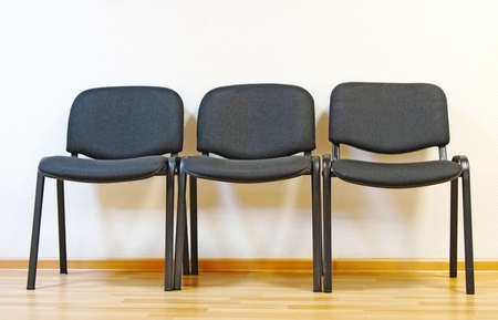 front office: Three black office chairs at an empty wall