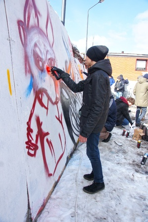MOSCOW - MARCH 17:  Participants of competition draw on a wall of graffiti at the first stage of city festival Graffiti jam. on MARCH 17, 2012 in Moscow, Design factory Bottle. Stock Photo - 12716607