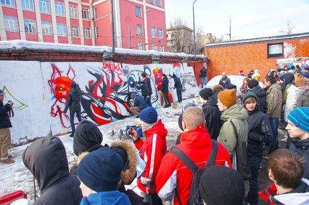 MOSCOW - MARCH 17:  Spectators look at participants of competition of graffiti at the first stage of city festival Graffiti jam. on MARCH 17, 2012 in Moscow, Design factory Bottle.