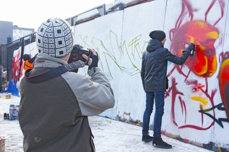 MOSCOW - MARCH 17:  Participants of competition draw on a wall of graffiti at the first stage of city festival Graffiti jam. on MARCH 17, 2012 in Moscow, Design factory Bottle. Stock Photo - 12716623