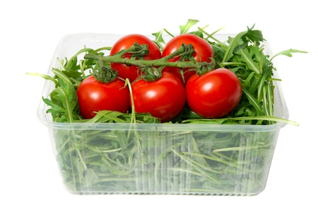 red tomatoes and green arugula, isolated on the white photo