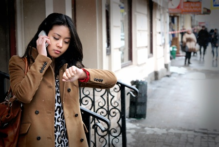 The beautiful Asian girl speaks by phone and looks at the watch photo