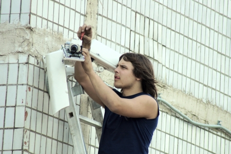 26_04_2012 Moscow, Russia. The young master establishes a video camera of external supervision on a building wall.
