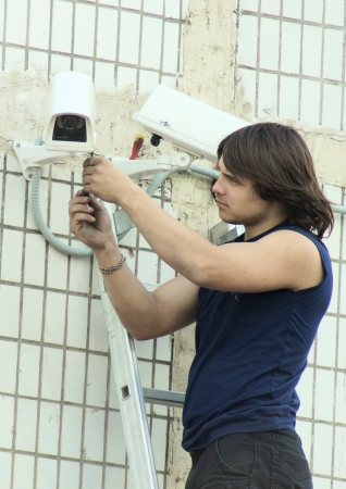 establishes: 26_04_2012 Moscow, Russia. The young master establishes a video camera of external supervision on a building wall.