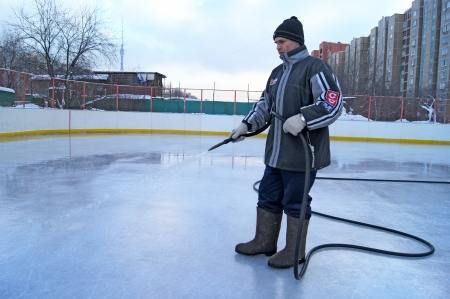 18_01_2012 Moscow, Russia. The man fills in street a hockey skating rink from a water hose.