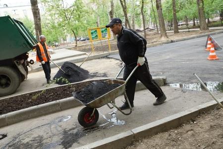 maquinaria pesada: 14_05_2012 Moscú, Rusia. Trabajadores que reparan carreteras de asfalto que cubre