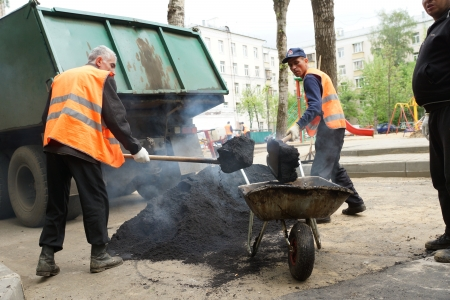 hard way: 14_05_2012 Moscow, Russia. Road workers repair an asphalt covering