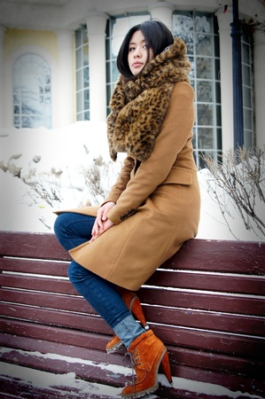 The fine Vietnamese girl sits in the winter on a bench in park photo