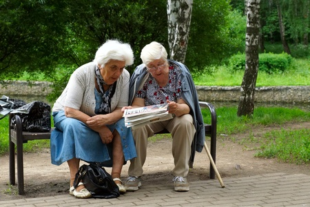 15 06 2012 Moscow, forest park. Pensioners excitedly read the newspaper.