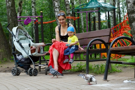 15 06 2012 Moscow, Medvedkovsky forest park. the woman with the child and a baby carriage on a bench.
