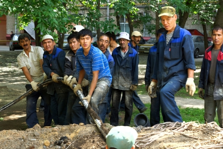 20 06 2012 Moscow. The brigade of labor migrants lays an electric cable.