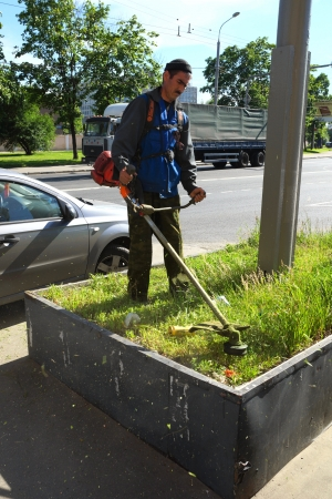 20.06.2012 Moscow. The worker mows a grass. Editorial