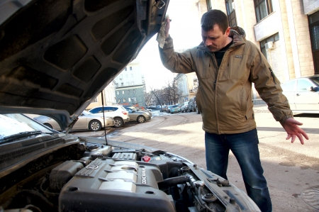 car trouble: 15.11.2012 Moscow. The driver examines the drive of the broken car.