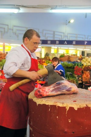 07.04.2012 Moscow. Cutting of a meat carcass in the grocery market.