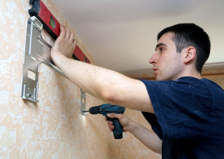 real photo of installation of the conditioner, fastening to a wall Stock Photo - 16431862
