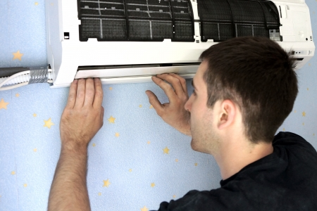 condition:  installation of the air conditioner, the worker establishes the internal module Stock Photo