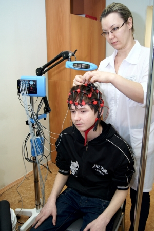 26.01.2012 Moscow. The doctor does the encephalogram to the patient.
