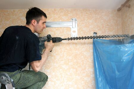 real photo of installation of the conditioner, the worker drills a hole in a wall photo