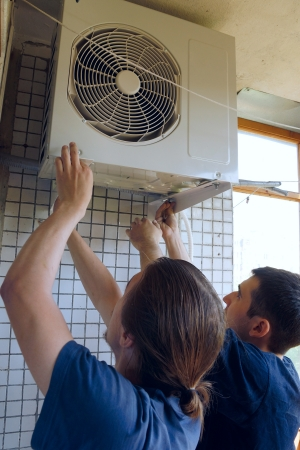 Two workers install air conditioning photo